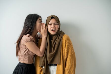 young girl whispered to the veiled girl with a shocked expression