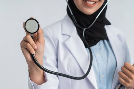 female doctor hijab using stethoscope and smile to camera over white background