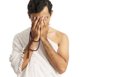 Muslim man praying wearing ihram isolated