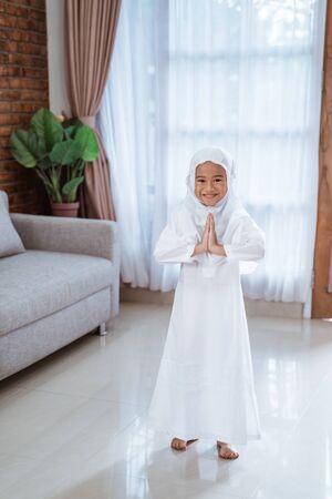 beautiful muslim toddler smiling with greeting gesture