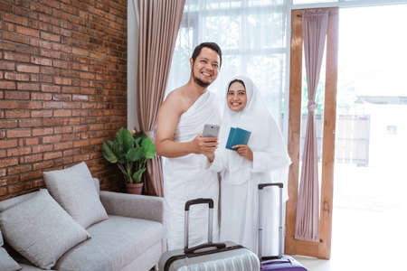 muslim couple making a phone call while umrah and hajj