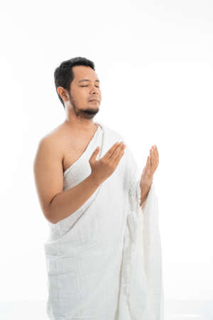 Muslim man praying in white traditional clothes