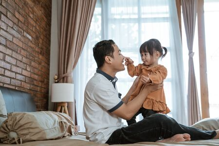 father laughed happily when his nose was touched by the little girl Stock fotó