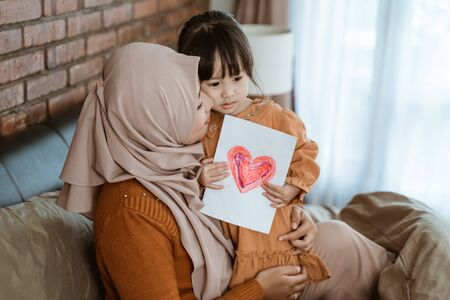 veiled mother kissed the little girl while hugging and holding heart printed paper