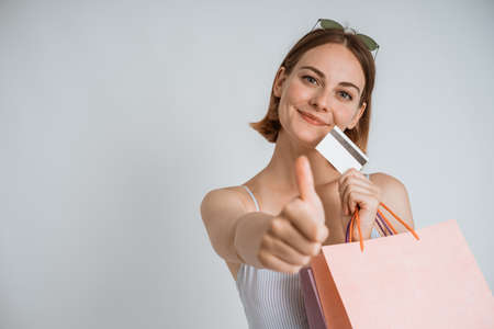 brunette holding shopping bags and credit card smiling