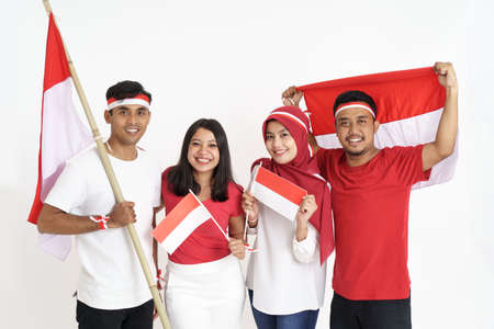 four friends together holding indonesian flag celebrating independence day