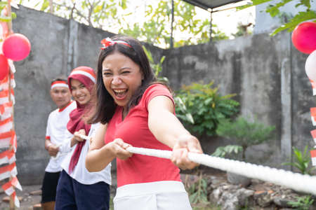 Asian young women shout with enthusiasm when pull the rope during the tug of war game