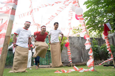 three young men happily joined in sack race jumping quickly to reach the finish line