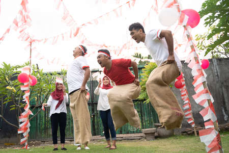 Sack race participants jumped each other by jumping to quickly reach the finish line