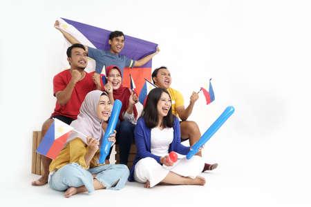 filipino group of people holding philippines flag celebrating