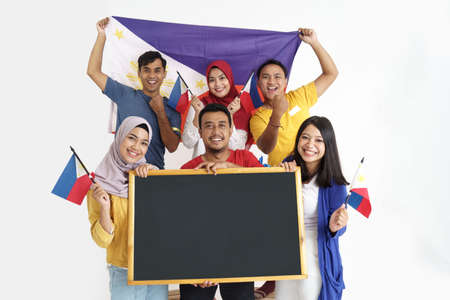 excited asian supporter holding philippines flag and blank blackboard