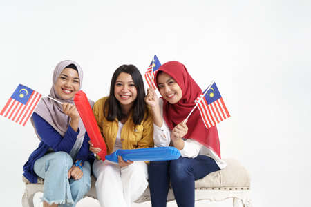 malaysia woman friend holding flag celebrating independence