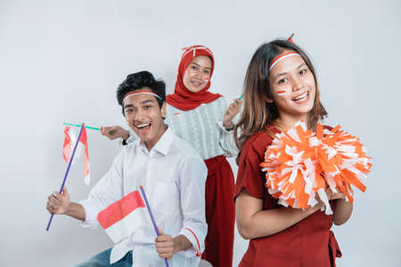 group of teenage wearing red and white attributes carrying pompom and Indonesian small flags