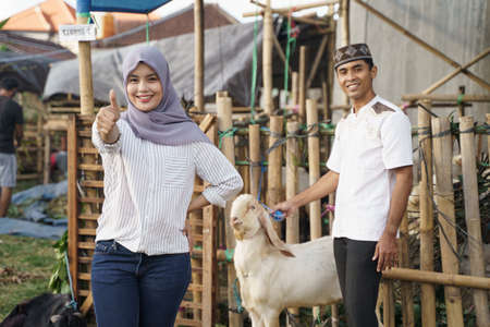muslim woman with scarf showing thumb up while standing in the goat farm
