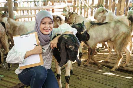 muslim female farmer doing check up for her goat Reklamní fotografie