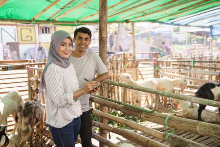 man and woman farmer at their farm checking the animal Stock Photo