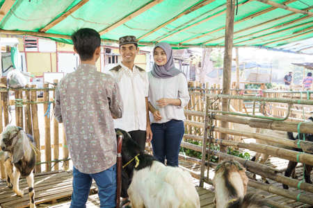 muslim people shake hand with farmer after buying a goat