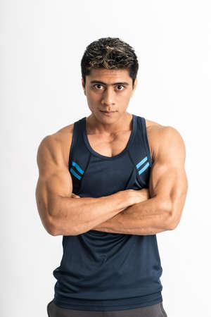 muscular man standing wearing gym clothes with crossed hands looking at the camera