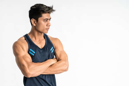 side view of muscular man standing wearing gym clothes with crossed hands look sideways
