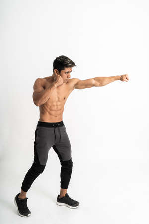 full body image of young man with muscular body with attacking movement with one hand punch