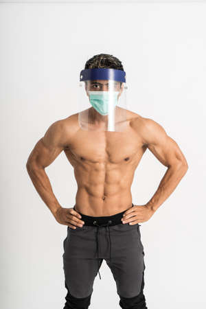 asian man show muscular bodies wearing a mask and face shield with two hands on waist stand facing forward and look to camera Stock Photo