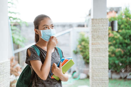 Asian student girl wears a mask with backpack take away books Foto de archivo