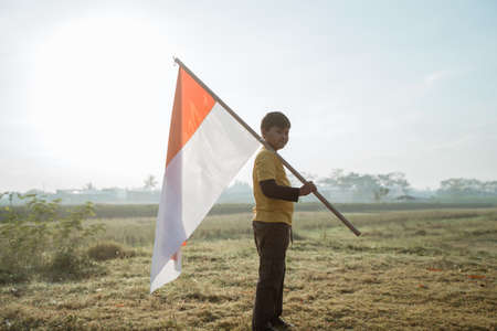 asian boy stand while carrying a large Indonesian flag on shoulder and look to camera 写真素材