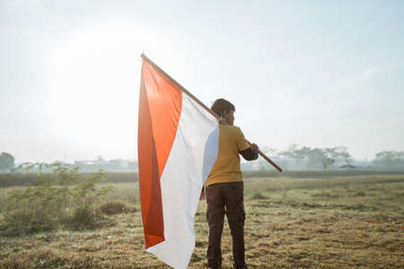 boy stand while carrying a large Indonesian flag on shoulder