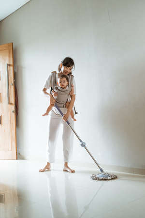 Asian Mom in white clothes with a baby in carrier baby mops the floor