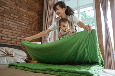 Asian mom carries the baby cleaning and arranges blanket