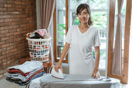 Smiling young woman ironing clothes