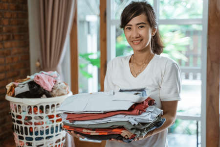 happy smiling Asian woman carrying laundry cloth basket Imagens