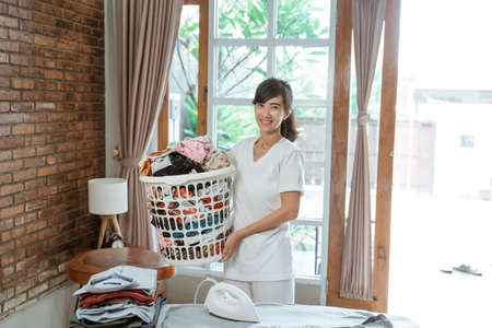 Pretty Asian woman at home holding basket of clean clothes