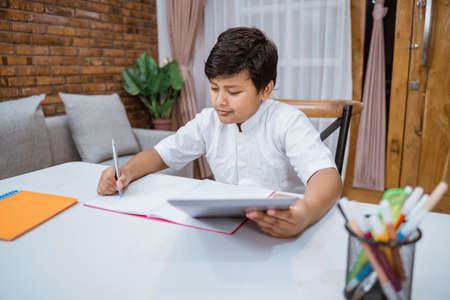 a boy concentrates on writing in notebooks and using digital tablets Banco de Imagens