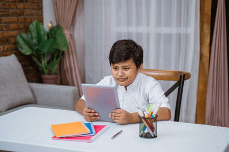 student boy with tablet pc sitting on the desk Stock Photo