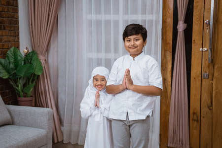 Muslim boy brothers and sisters greeted while standing in living room
