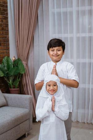 Asian boy brothers wearing a Koko shirt and sisters wearing veil say Salaam