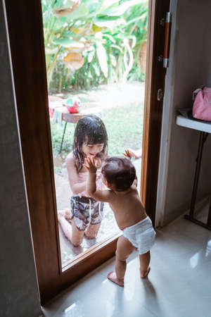 Two Asian siblings smiled at each other through the window glass