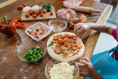 Photo of children hands cooking Italian food