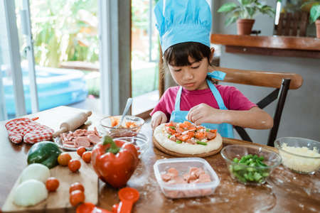 Cute little girl in Asian chief hat makes pizza with tomatoes and grated cheese