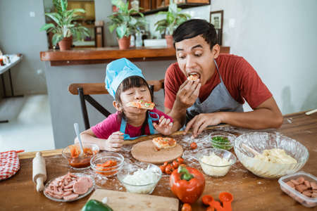 Portrait of happy father with child eating pizza