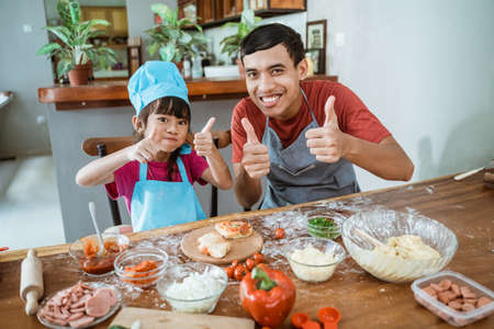 Cute dad with daughter with thumbs up when eating pizza
