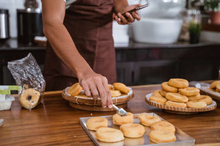 Hand of a man making homemade donut on wooden table Stockfoto
