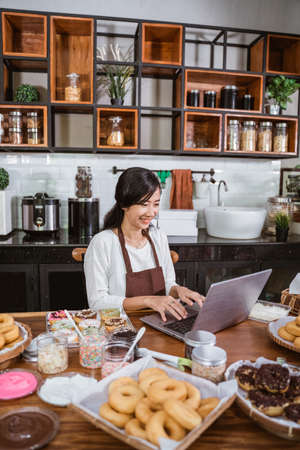 female chef wearing an apron while using a laptop