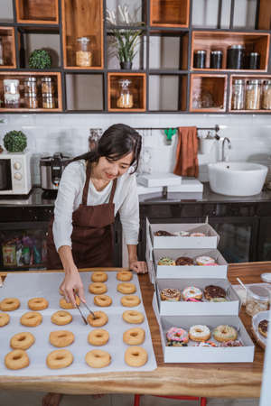 a beautiful woman wearing an apron while preparing donuts in packaging boxes with food clips Stockfoto