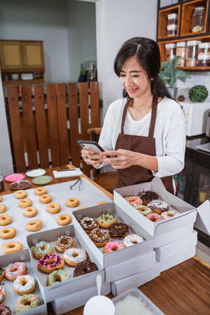 Asian woman wearing an apron using a smartphone to shoot a picture of donut when to sell online