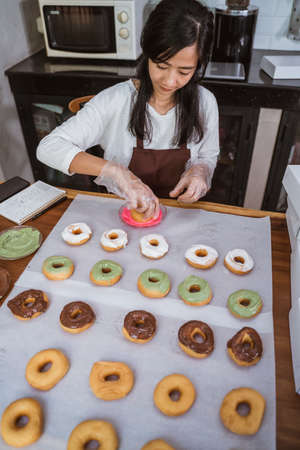 beautiful women wearing aprons and gloves while decorating various donuts with chocolate frosted