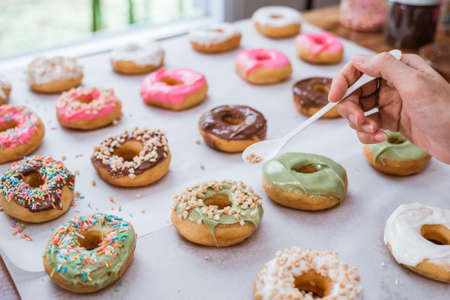close up of hands decorating various donuts with chocolate frosted, pink glazed and donut sprinkle