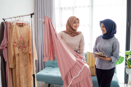 portraits of beautiful muslim women shopping for clothes and chatting with seller