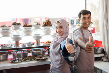 portrait of young man and female muslim working as traditional food seller Standard-Bild